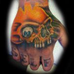 Orange skull hand tattoo